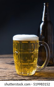 Mug fresh beer on wooden table with wood background and copyspace
