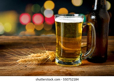 Mug of fresh beer and spikelet on the wooden table, Cold beer glass on bar or pub desk