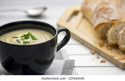 Mug full of fresh homemade potato soup garnished with cream and chives