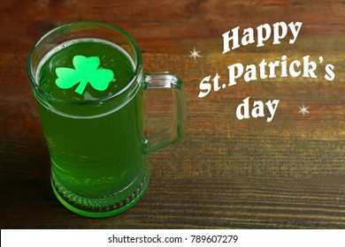Mug of green beer and clover on a wooden background. Concept day of St. Patrick.