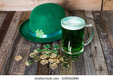 Mug of green beer with fun decoration on wooden background.