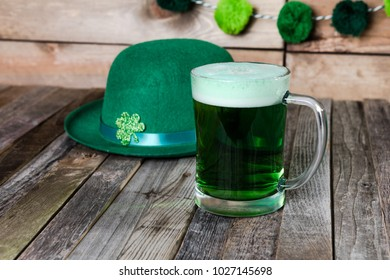 Mug of green beer with Irish festive hat on wooden background. Tabletop, front view.