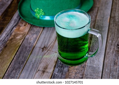 Mug of green beer with Irish festive hat on wooden background. Tabletop, side view.