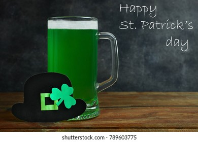 Mug of green beer on a black background. Concept day of St. Patrick.