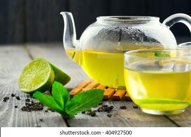 Mug of green tea and teapot on wood table