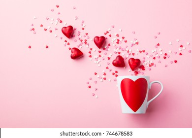 Mug with heart with sugar and chocolate hearts on pink background. Flat lay composition. Romantic, St Valentines Day concept.