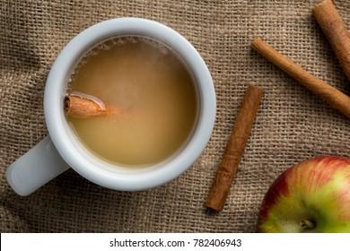 A mug of hot apple cider with cinnamon sticks.