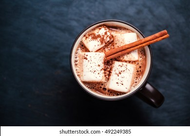 Mug of hot chocolate with cinnamon stick over dark background. Hot cocoa