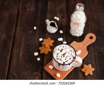 Mug of hot chocolate or cocoa with Christmas cookies and marsmallow on dark wooden background