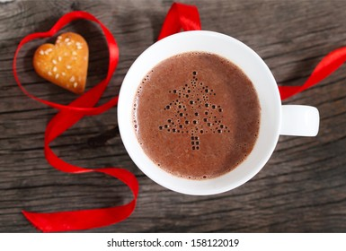 Mug of hot chocolate or cocoa with cookies decorated by red ribbon