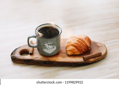Mug of hot coffee and croissant on a wooden tray. breakfast concept