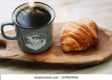 Mug of hot coffee and croissant on a wooden tray. breakfast concept. good morning