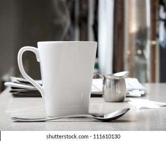 Mug of hot coffee or tea with stainless creamer and morning newspaper on counter. Intentionally desaturated for effect