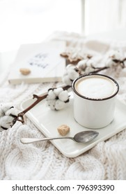 Mug of hot drink with cotton branch on white cozy winter blanket