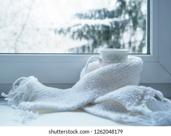 Mug of hot tea and warm woolen knitting on windowsill against snow landscape from outside.