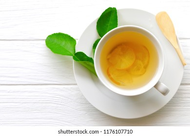 A mug of Lemon tea with honey on white wooden floor at top view.