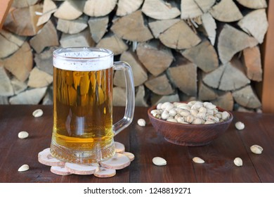 Mug of light beer on the table against the background of firewood.