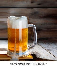 Mug of light beer on a wooden table, rustic style