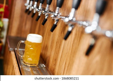 a mug of light beer stands on a stand under the beer taps in a beer pub. - Shutterstock ID 1868085211