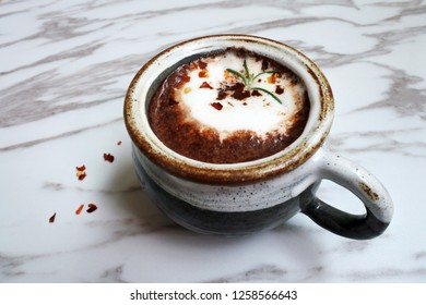 a mug of Mexican spicy chili flake hot chocolate on marble table