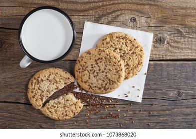 Mug with milk and cookies with flax seeds and sesame on old wooden table, top view