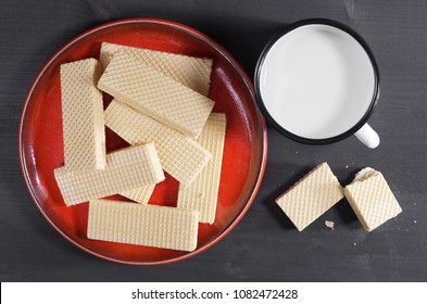 Mug of milk with waffles in red plate on black wooden background, top view
