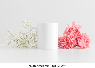 Mug mockup with a bouquet of pink carnations and a gypsophila on a white table.
