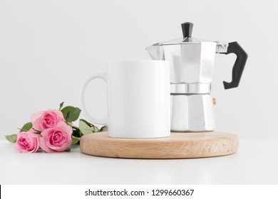Mug mockup with moka pot and a bouquet of pink roses on a white table.