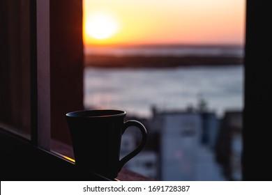 Mug on the window and blurred sunset background