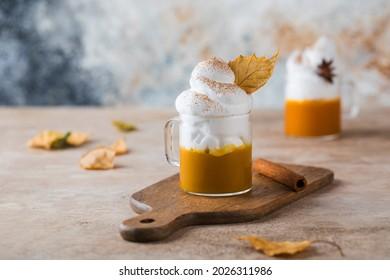 Mug of pumpkin coffee with whipped cream and dry leaf