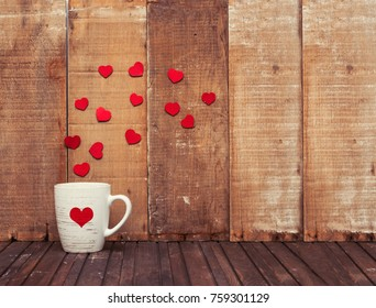 A mug and red hearts on wooden background