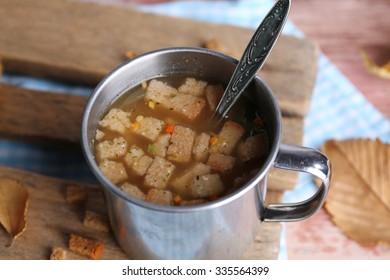 Mug of soup on wooden mat