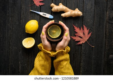 Mug of tea in female hands. Lemon, ginger and thermometer. Cold treatment. Wooden background. Top view