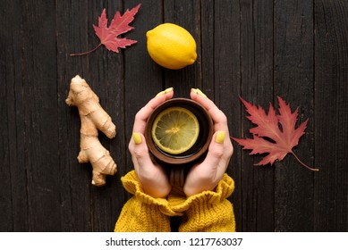 Mug of tea in female hands. Lemon, ginger and autumn leaves. Cold treatment. Wooden background. Top view