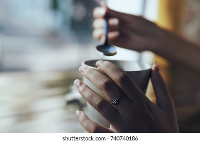 mug of tea, in the hand a spoon close-up