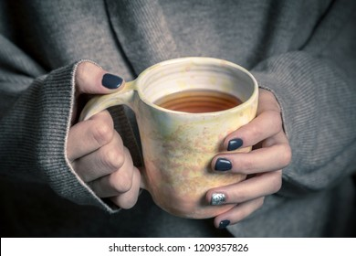 mug of tea in the hands of a girl in a sweater