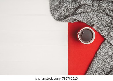 Mug with tea and home decor on white, cosy wooden table background. Winter morning relax concept, top view. Frame with cup and copy space around objects.