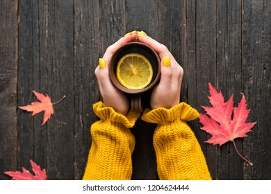 Mug of tea with lemon in a female hand. Wooden background, autumn leaves. Top view