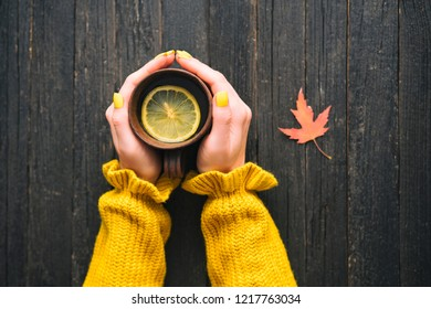 Mug of tea with lemon in a female hand. Wooden background, autumn leaf. Top view
