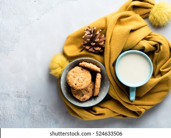 Mug of tea with milk and cookies with chocolate chips in a soft yellow winter scarf on gray background. Coffee break for home relax. Top view