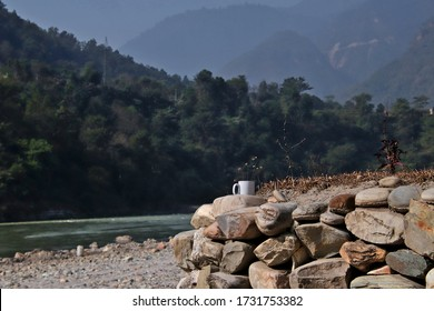 A mug of tea on stones on the riverbank of the Trishuli river in Nepal, with forested hills in the background