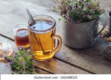Mug of thyme healthy herbal tea, honey jar and rustic metal cup full of thymus serpyllum medicinal herbs.