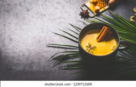 Mug of vegan golden turmeric milk with spices: cardamon, anise and cinnamon  on dark background with ingredients and palm leaves. Healthy hot drink. Immune boosting remedy , detox and dieting concept