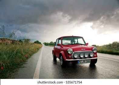 Mugello, Italy - May, 2013: Red classic Austin Mini Cooper retro vehicle parked on the road on a cloudy day at the International Mini Meeting 2013 in Mugello, Italy.