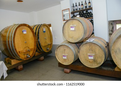 stacked oak barrels maturing red wine. Stacked Oak Barrels For Maturing Red Wine. Muggio Valley, Switzerland - 8 May 2018: Wine In Cellar. Cavernous C