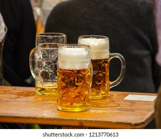 Mugs of Bavarian beer on a wooden desk, closeup view. Oktoberfest, Munich, Germany.