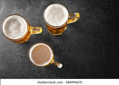 Mugs with beer on table
