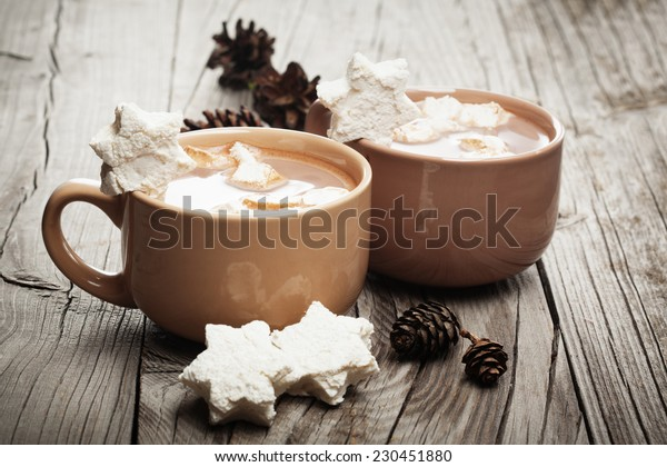 Mugs filled with hot chocolate and marshmallows on old wooden background, Christmas time