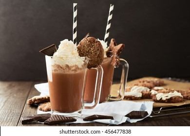 Mugs of Hot Chocolate with Whipped Cream and Homemade Biscuit Cookies on old wooden background, selective focus