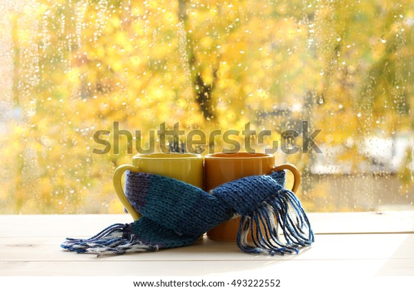 mugs tied together warming scarf on the background of a wet window after the rain / warm drinks for the autumn mood